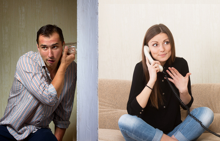 Man with a glass listening to the girl's phone conversation through the wall Archivio Fotografico