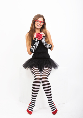 women legs: Smiling girl in black and white striped tights with the gift box