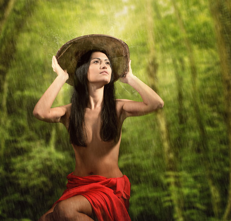 half naked: Portrait of a pretty half naked woman with bamboo hat, rainy jungle background