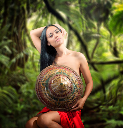 half naked: Portrait of a pretty half naked woman with bamboo hat, jungle background