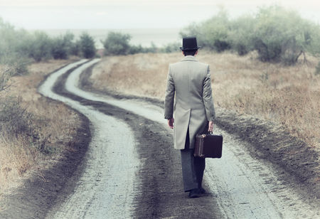 maleta: Hombre del estilo retro en la carretera del país, vista desde atrás