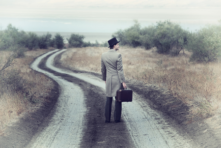 Retro style man on the country road, view from back Stock Photo