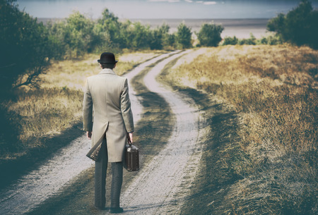 gentleman: Retro style man on the country road, view from back Stock Photo