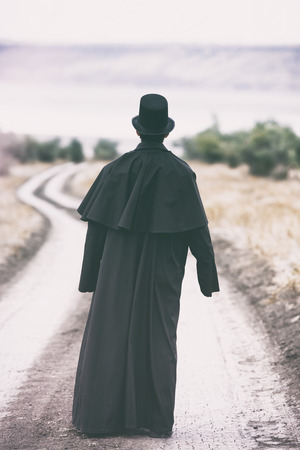 historical periods: Stylized portrait of a man in garrick coat walking on the rural path Stock Photo