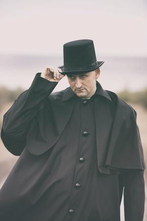 vestidos de epoca: estilizado retrato de un hombre hosco en el abrigo de Garrick y sombrero de copa Foto de archivo
