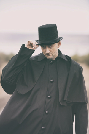 historical periods: Stylized portrait of a sullen man in garrick coat and top hat Stock Photo