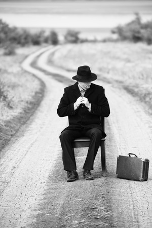 personas en la calle: Hombre del estilo retro sentado en una silla en medio de la carretera nacional, foto en blanco y negro Foto de archivo