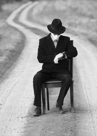 black hat: Man in the mask sitting on a chair in the middle of the country road, black and white shot Stock Photo