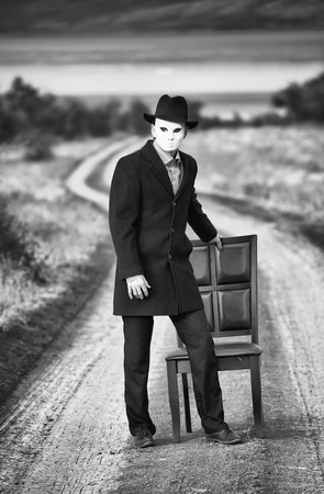 white mask: Man in the mask standing near the chair on the country road, black and white shot