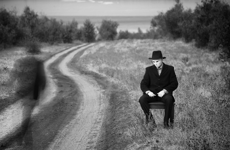 unknown age: Man in the mask sitting on a chair by the side of the country road, black and white shot
