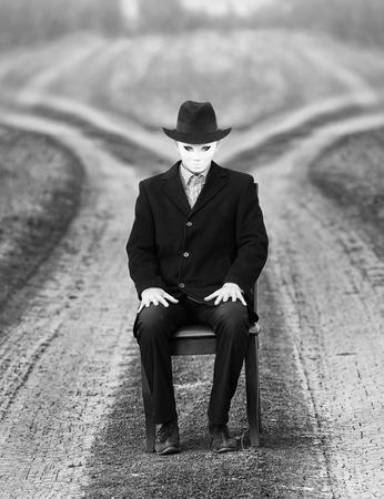 hombre con sombrero: Hombre en la máscara que se sienta en una silla frente a dos caminos