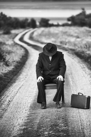 old suitcase: Retro style man sitting on a chair in the middle of the country road, black and white shot