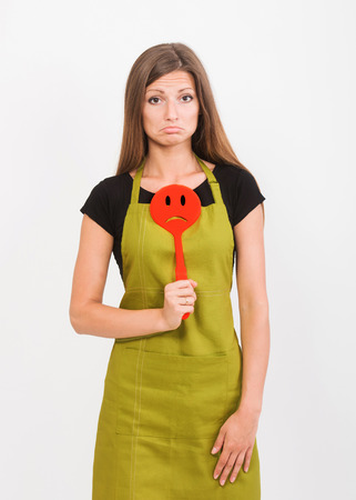 inexperienced: Girl in yellow apron with a sad face spatula