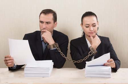Couple with chained hands reading a contract, concept