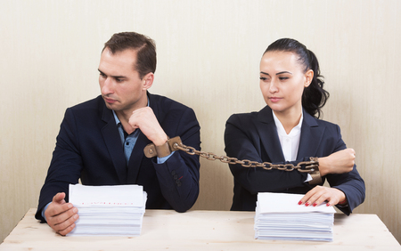 constrained: Couple with chained hands reading a contract, concept