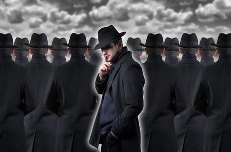 silencio: Hombre misterioso que hace un gesto de silencio mientras está de pie entre la multitud