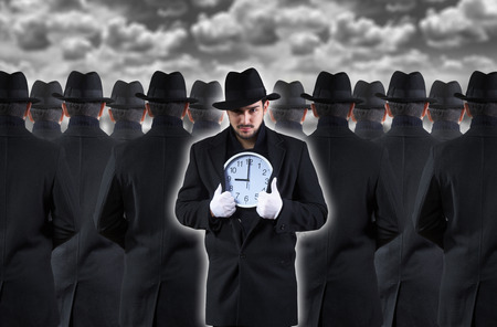 strangers: Man showing the clock while standing out from the crowd