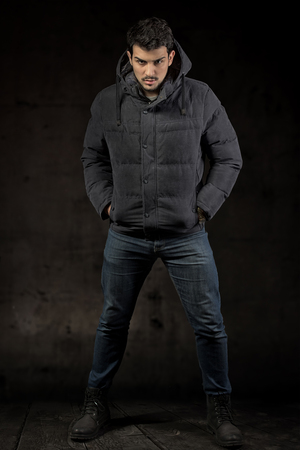black male: Full length portrait of a man wearing the winter jacket, dark background