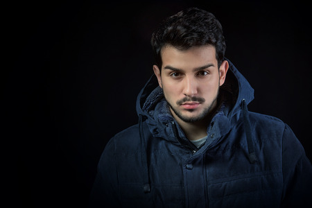 brunets: Man in winter jacket, studio shot, dark background