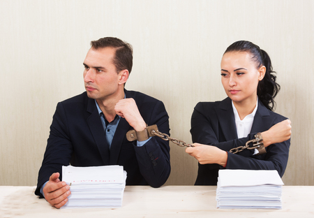 tied woman: Couple with chained hands reading a contract, concept