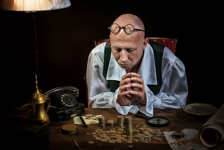 antiquary: Antiquarian looking at the old coins Stock Photo