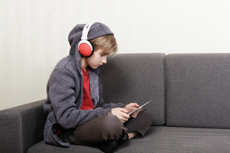 alone boy: Boy with a digital tablet sitting on the couch