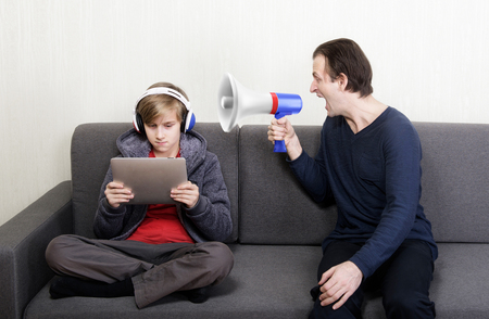 boy sitting: Tween son in headphones looks at the digital tablet display while his father yells at him through a megaphone Stock Photo