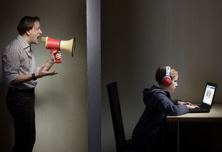 tween: Tween son in headphones looks at a computer screen while his father yells at him through a megaphone