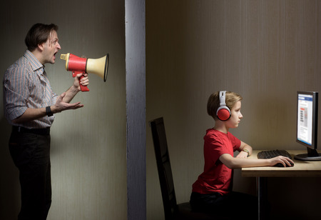 indifferent: Tween son in headphones looks at a computer screen while his father yells at him through a megaphone