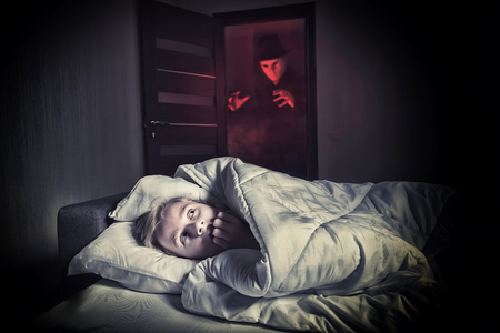 scared boy: Nightmare. Scared boy lying in the bed while the masked stranger standing in a doorway