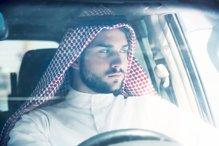 shemagh: Portrait of a handsome arabian man driving a car