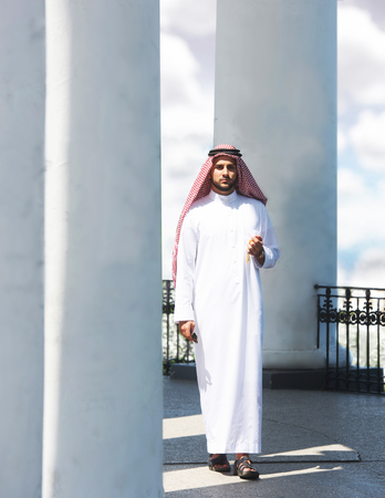 shemagh: Portrait of a handsome arabian man walking among the columns