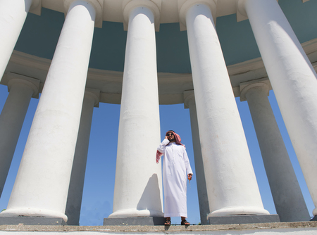shemagh: Arabian man standing in front of large columns, view from below Stock Photo