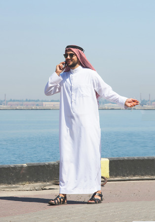 shemagh: Arabian man talking on the cell phone in the port