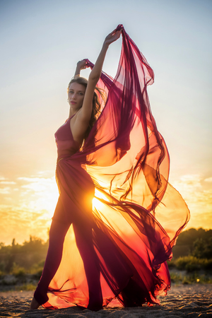 gauzy: Girl in airy dress posing at sunset Stock Photo