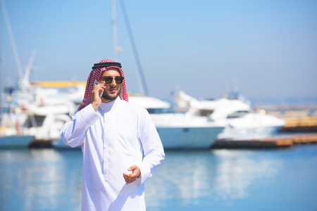 shemagh: Arabian man talking on the cell phone at the yacht harbor Stock Photo