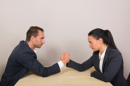 battle of the sexes: Businesswoman vs businessman - arm wrestling on working table Stock Photo