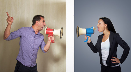 severance: Man and woman shouting in megaphones at each other Stock Photo