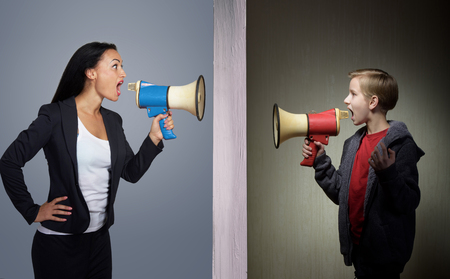 psicologia infantil: Tween hijo y su madre gritando a través de los megáfonos el uno al otro