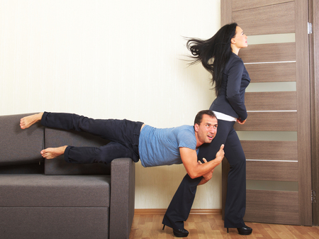 clinging: Man desperately clinging to the leg of a woman