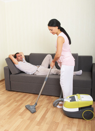 slacker: Woman vacuuming while man is resting on a couch