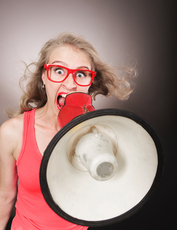 outcry: Funny portrait of a girl shouting through the megaphone