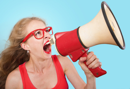 Funny portrait of a girl shouting through the megaphone