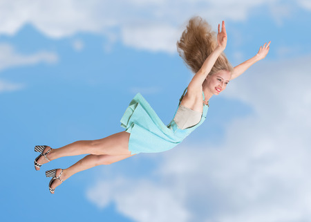levitation: Happy young woman flying in the sky Stock Photo