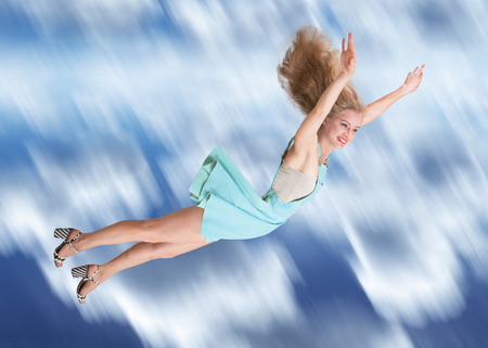 flying woman: Happy young woman flying in the sky Stock Photo