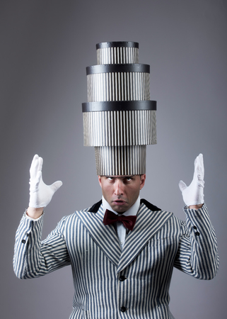 troubled: Pre-holiday fuss concept. Troubled man with the stacked gift boxes on his head