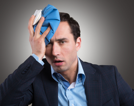 Office worker with an ice pack on his head Stock Photo