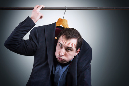 embarrassing: Man in suit hanging in the wardrobe. Embarrassing situation concept