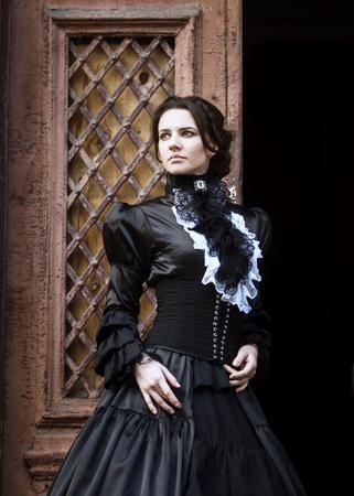 century: Lady in black standing in the doorway