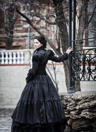 黒のビクトリア朝の女性の屋外ポートレート